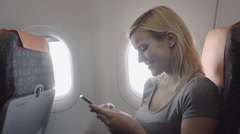 Single adult female on plane with smart phone technology Stock Footage