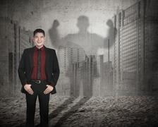Asian business man casting a shadow of strength Stock Photos