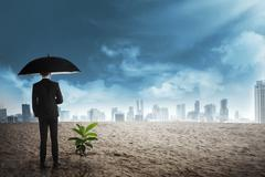 Asian business man in black umbrella stand beside plant seed grow on the dese Stock Photos