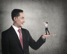 Giant businessman holding little man yelling with megaphone Stock Photos