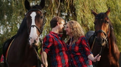 A young couple kissing in the park on the background of horses Stock Footage