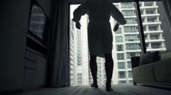 Young man in bathrobe stretching arms close to the window, slow motion 240fps Stock Footage