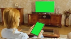 Girl Using Tablet In Front Of The TV 1 With Green Screen Stock Footage