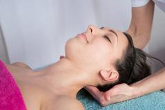 A woman getting a stress relieving pressure point massage on her neck by a he Stock Photos
