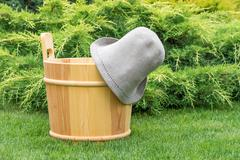 Wooden bucket and felt hat for the sauna. Stock Photos