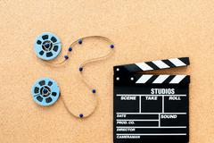 Two little movie reel connected with filmstrip path - stock photo