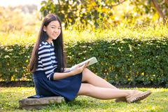 portrait of asian teen twelve years old and school book in hand with toothy s - stock photo