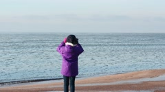 Warmly clothed Little girl with binoculars  at winter sea shore Stock Footage