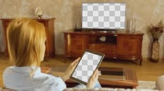 Girl Using Tablet In Front Of The TV 1 With Isolated Screen Stock Footage