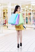 Joyful model carries shopping bags at mall - stock photo
