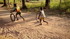 Africa kids playing with bike wheels Stock Footage