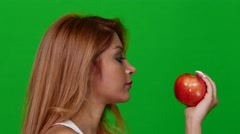 Side Angle of Woman Eating an Apple on Green Screen Stock Footage