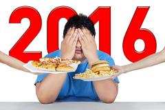 Overweight man with numbers 2016 refuses junk food Stock Photos