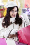 Teenage girl looking at shopping bags at mall - stock photo