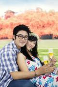 Young couple drinking champagne at the park - stock photo