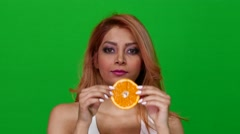 Woman Eating an Orange Slice on Green Screen Stock Footage