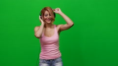 Woman Listening to Music on Green Screen Stock Footage