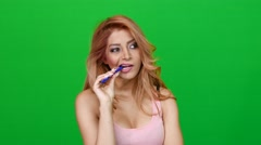 Woman Playing with a Pen on Green Screen Stock Footage