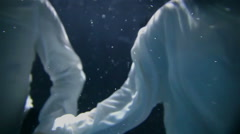 A young couple is holding hands and swimming under water Stock Footage