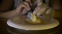 A chef puts the finishing touches on a dessert by drizzling sauce from bottle Stock Footage