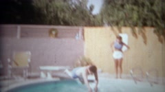 1965: Man falls off springboard in failed attempt at pool diving fun.  SAN Stock Footage