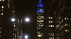 Close-up of Empire State Building at night blue lights, tilting down 8th Ave NYC Stock Footage