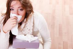 Stock Photo of Sick woman girl with fever sneezing in tissue
