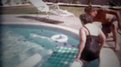 1965: Old women helped into pool lounger floating chair enjoys summer sun. SAN Stock Footage