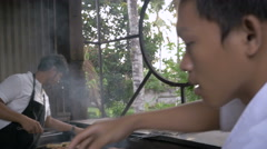 Hand held shot of 3 people working together at a busy outdoor grill Stock Footage