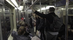 Man standing holding onto poles on moving subway train, passengers seated 4K NYC Stock Footage