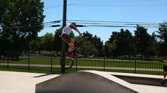 Teen doing a backwards stunt on his BMX bike Stock Footage