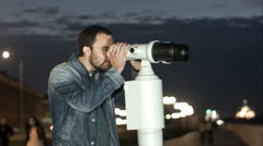 Man using a coin operated telescope enjoying a great view of the city Stock Footage