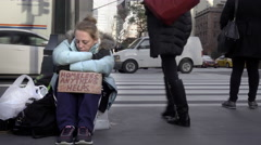 Homeless woman with help sign on cold fall winter day sitting Park Avenue 4K NYC Stock Footage