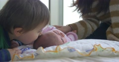 2 year old brother kisses his new born baby sister Stock Footage