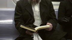 Religious Jewish man in hat reading Torah book on New York City subway train NYC Stock Footage