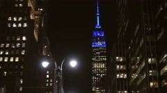 Zooming out Empire State Building close-up at night Eighth Ave crosswalk NYC 4K Stock Footage