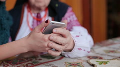 Granddaughter assisting senior woman in using smartphone at nursing home porch - stock footage