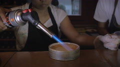 A chef uses a hand torch to caramelize the top of creme brûlée Stock Footage