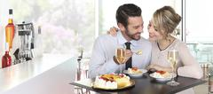 Happy couple date at the bar with wine and fruit cake, love concept Stock Photos