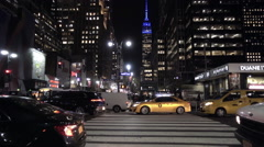 cars and taxi cabs driving 8th ave traffic night life Empire State Building NYC - stock footage