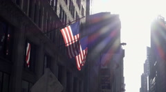 American flags on building panning down to pedestrians waiting cross street NYC Stock Footage