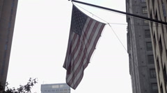 American flag waving building overhead panning down people walking Park Ave NYC Stock Footage