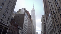 Beautiful wide shot of Empire State Building tilting down people crosswalk NYC Stock Footage