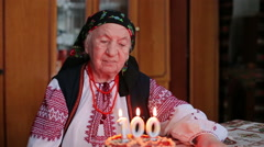 happy hundred years old lady blows 100 candles in a rush on a birthday cake - stock footage