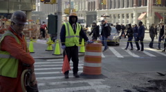 City construction workers in orange suits and helmets drilling into street NYC Stock Footage