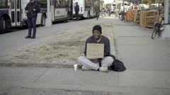 Homeless black man with thyroid illness sign begging for change at Cooper Square Stock Footage