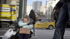 Man giving homeless woman with sign a dollar on Park Ave with Met Life Building Stock Footage