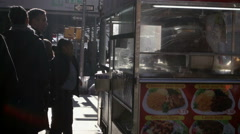 People on line in close-up of food cart in Midtown Manhattan on cold fall winter Stock Footage