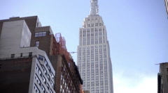 Tight shot on Empire State Building tilting down east 34th st USPS truck NYC Stock Footage