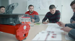 An engineer is explaining something in a meeting to other engineers Stock Footage